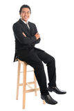 Full body Asian businessman arm crossed sitting on chair Royalty Free Stock Images