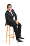 Full body Asian businessman seated on chair Royalty Free Stock Image