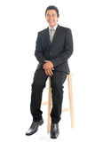 Full body Asian businessman sitting on chair. Full body portrait of happy young Southeast Asian businessman sitting on high chair, isolated on white background Royalty Free Stock Photography
