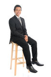 Full body Asian businessman sitting on high chair Royalty Free Stock Photo