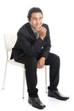 Full body Asian businessman sitting on white chair and thinking Stock Photo