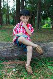 Full body. Asisn child thoughtful on wooden log in national park Royalty Free Stock Photography