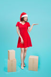 Full-body of attractive cheerful asian girl in Santa`s hat point royalty free stock image