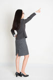 Full body backside Asian business woman pointing. At copy space, standing on plain background Royalty Free Stock Photo