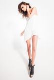 Full body of beautiful woman model posing in white dress in the studio. Full body of beautiful woman model posing in white dress Stock Photo