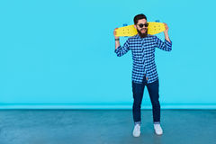 Full body of Casual handsome attractive man hipster guy. Holding a yellow skateboard over blue background with copy space Stock Photos