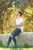 Full body cheerful man sitting on wall in park with cellphone Royalty Free Stock Images