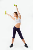 Full body of cheerful woman in fitness wear exercising with dumbbells, isolated over white background Royalty Free Stock Images
