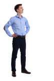 Full body of a confident casual business man looking up. With his hands on hips. Isolated Stock Images