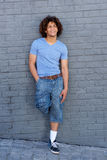 Full body cool young guy with curly hair smiling Stock Images