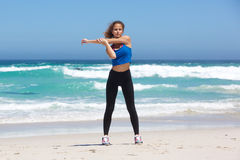 Full body fit young woman stretching at beach Royalty Free Stock Image