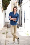 Full body handsome young man standing on city street with arms crossed Royalty Free Stock Photo