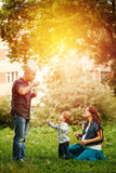 Full-body of happy family in city park at the sunset.  Royalty Free Stock Photos