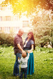 Full-body of happy family in city park at the sunset. Mother, father and little son Royalty Free Stock Photos