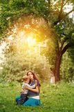 Full-body of happy family in city park at the sunset. Mother and son Stock Images