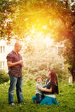 Full-body of happy family in city park at the sunset. Playing together Royalty Free Stock Photography