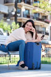 Full body happy woman sitting on bench with luggage and phone Royalty Free Stock Photography
