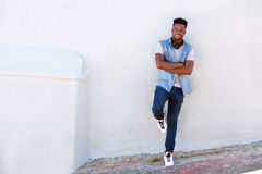Full body happy young man leaning against wall with headphones. Full body portrait of happy young man leaning against wall with headphones Stock Photos