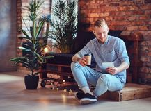 The full body image of blond stylish male using a tablet PC. The full body image of blond stylish male dressed in a fleece shirt and jeans using a tablet PC and Royalty Free Stock Image