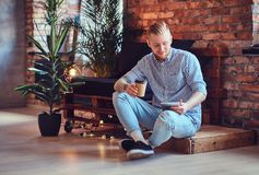 The full body image of blond stylish male using a tablet PC. The full body image of blond stylish male dressed in a fleece shirt and jeans using a tablet PC and Stock Photo