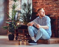 The full body image of blond stylish male using a tablet PC. The full body image of blond stylish male dressed in a fleece shirt and jeans using a tablet PC in Royalty Free Stock Images