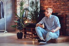 The full body image of blond stylish male using a tablet PC. The full body image of blond stylish male dressed in a fleece shirt and jeans using a tablet PC and Royalty Free Stock Photos