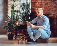 The full body image of blond stylish male using a tablet PC. The full body image of blond stylish male dressed in a fleece shirt and jeans using a tablet PC in Stock Photo