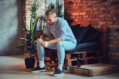 The full body image of blond stylish male using a tablet PC. The full body image of blond stylish male dressed in a fleece shirt and jeans using a tablet PC in Royalty Free Stock Image