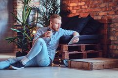 The full body image of blond stylish male using a tablet PC. The full body image of blond stylish male dressed in a fleece shirt and jeans using a tablet PC in Royalty Free Stock Photography