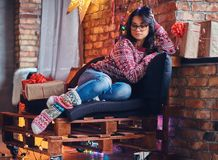 Brunette female in a room with Christmas decoration. Full body image of brunette female in eyeglasses dressed in a jeans and a red sweater posing on a wooden Royalty Free Stock Photos