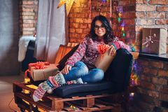 Brunette female in a room with Christmas decoration. Full body image of brunette female in eyeglasses dressed in a jeans and a red sweater posing on a wooden Royalty Free Stock Image