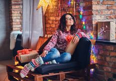 Brunette female in a room with Christmas decoration. Full body image of brunette female in eyeglasses dressed in a jeans and a red sweater posing on a wooden Stock Photos