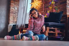 Brunette female in a room with Christmas decoration. Full body image of sexy brunette femalesits on a floor in a room with Christmas decoration Stock Photography