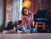 Brunette female in a room with Christmas decoration. Full body image of sexy brunette femalesits on a floor in a room with Christmas decoration Stock Photo