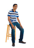 Full body indian man sitting on a chair over white background Stock Images