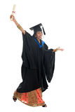 Full body Indian university student jumping. Full length happy Indian university student in graduation gown and cap holding diploma certificate jumping. Portrait Stock Image