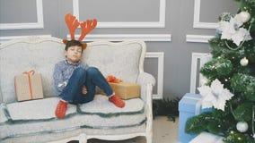 Full-body lovely video of little boy with reindeer headgear, sleeping on the sofa among Christmas presenst near fir-tree