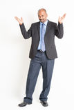 Full body mature Indian businessman open arms and showing someth Royalty Free Stock Photo