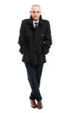 Full body of middle age business man posing wearing overcoat. Full body of middle age business man standing with legs crossed wearing overcoat isolated on white Royalty Free Stock Photo