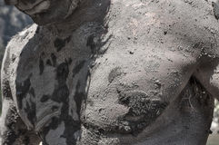 Full body mud therapy. Closeup of upper torso chest area of muscular man covered in dry cracking mud outdoors in direct sunlight stock photography