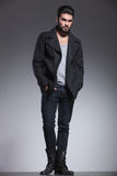 Full body picture of a fashion man with beard looking away. Full body picture of a fashion man with beard standing with hands in pockets and looking away from royalty free stock image