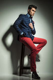 Full body picture of a fashion man sitting Stock Images