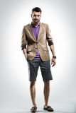 Full body picture of fashionable man with a beard. Against studio wall stock photo