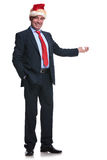 Full body picture of a mature business man santa presenting Royalty Free Stock Image