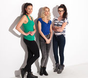 Full body picture of three young casual women. Posing in studio, lookinf to side stock photos