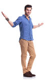 Full body picture of a young casual man welcoming Royalty Free Stock Images