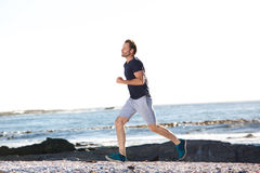 Full body portrait of active man running by beach Royalty Free Stock Photos