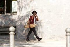 Full body african guy with skateboard walking outside using mobile phone. Full body portrait of african guy with skateboard walking outside using mobile phone Stock Image