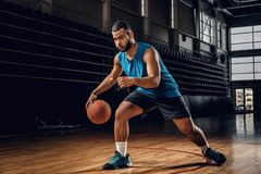 Professional basketball player in an action in basketball field. Full body portrait of Black professional basketball player in an action in basketball field Royalty Free Stock Images