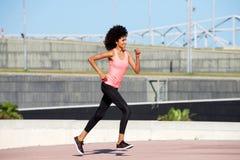 Full body female runner outside for exercise routine Stock Photos